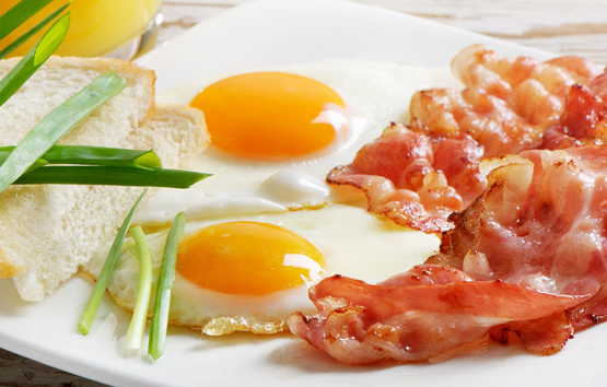 Traditional breakfast with bacon and fried eggs